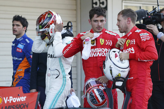 Ferrari driver Sebastian Vettel of Germany, right, talks with teammate Charles Leclerc of Monaco as Mercedes driver Lewis Hamilton of Britain prepares to put off his helmet after the Japanese Formula One Grand Prix at Suzuka Circuit in Suzuka, central Japan, Sunday, Oct. 13, 2019. (AP Photo/Toru Hanai)