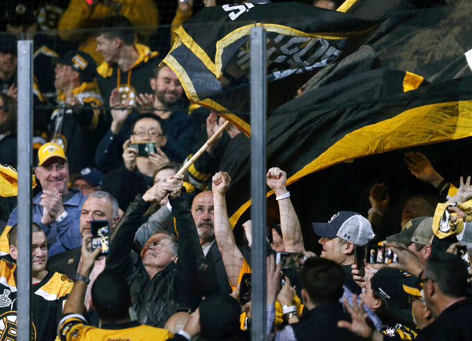 New England Patriots head coach Bill Belichick, lower left, waves the Boston Bruins banner before Game 2 of the NHL hockey Stanley Cup Final between Bruins and the St. Louis Blues, Wednesday, May 29, 2019, in Boston. (AP Photo/Michael Dwyer)