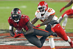 Tampa Bay Buccaneers wide receiver Chris Godwin (14) makes a diving catch in front of Kansas City Chiefs cornerback Rashad Fenton (27) during the second half of an NFL football game Sunday, Nov. 29, 2020, in Tampa, Fla. (AP Photo/Jason Behnken)
