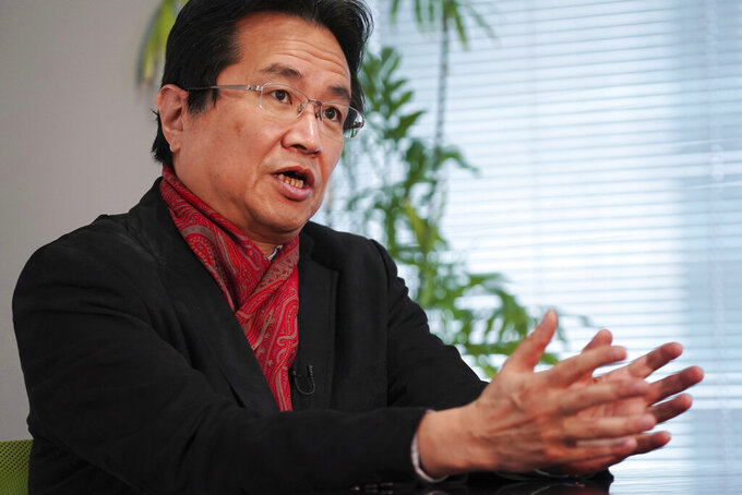 Writer Ryu Honma speaks during an interview with The Associated Press in Tokyo Thursday, Nov. 12, 2020. Honma, who has written several books critical of the Olympics and Dentsu's ties to Tokyo's bid, said Games will be a farce.(AP Photo/Eugene Hoshiko)