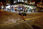 A protester uses a plate to cover a tear gas during clashes with policemen near the Shum Shui Po police station in Hong Kong on Wednesday, Aug. 14, 2019. German Chancellor Angela Merkel is calling for a peaceful solution to the unrest in Hong Kong amid fears China could use force to quell pro-democracy protests. (AP Photo/Vincent Yu)
