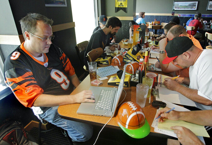 FILE - This Aug. 30, 2010, file photo shows Brian Sherman, left, using his laptop to record moves in his team's fantasy football draft, at a Buffalo Wild Wings restaurant in Cincinnati. From 2007 to 2017, the number of people playing fantasy football more than tripled, from 13.8 million to 42.7 million, according to the Fantasy Sports & Gaming Association. This past Sunday, ESPN's fantasy app drew 8.3 million unique users _ its biggest day ever _ according to ESPN and Adobe Analytics (AP Photo/Al Behrman, File)