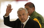 Mexican President Andres Manuel Lopez Obrador waves as he leaves after giving his daily, morning press conference, in front of the former presidential plane at Benito Juarez International Airport in Mexico City, Monday, July 27, 2020. The president, who only flies commercial as one measure in his austerity government, has been trying to sell the plane since he took office. (AP Photo/Marco Ugarte)