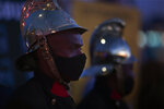 Firemen join frontline workers at a candlelight ceremony on New Year's Eve on the famed Nelson Mandela Bridge in downtown Johannesburg Thursday, Dec. 31, 2020. Many South Africans will swap firecrackers for candles to mark New Year's Eve amid COVID-19 restrictions including a nighttime curfew responding to President Cyril Ramaphosa's call to light a candle to honor those who have died in the COVID-19 pandemic and the health workers who are on the frontline of battling the disease. (AP Photo/Denis Farrell)