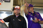 Denny Hamlin, left, talks to a crew member before practice for Sunday's NASCAR Cup Series auto race at the Circuit of the Americas in Austin, Texas, Saturday, May 22, 2021. (AP Photo/Chuck Burton)