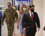 Arizona Gov. Doug Ducey, right, arrives to give an update on COVID-19 in Arizona during a news conference Wednesday, June 17, 2020 in Phoenix. (Michael Chow/The Arizona Republic via AP, Pool)