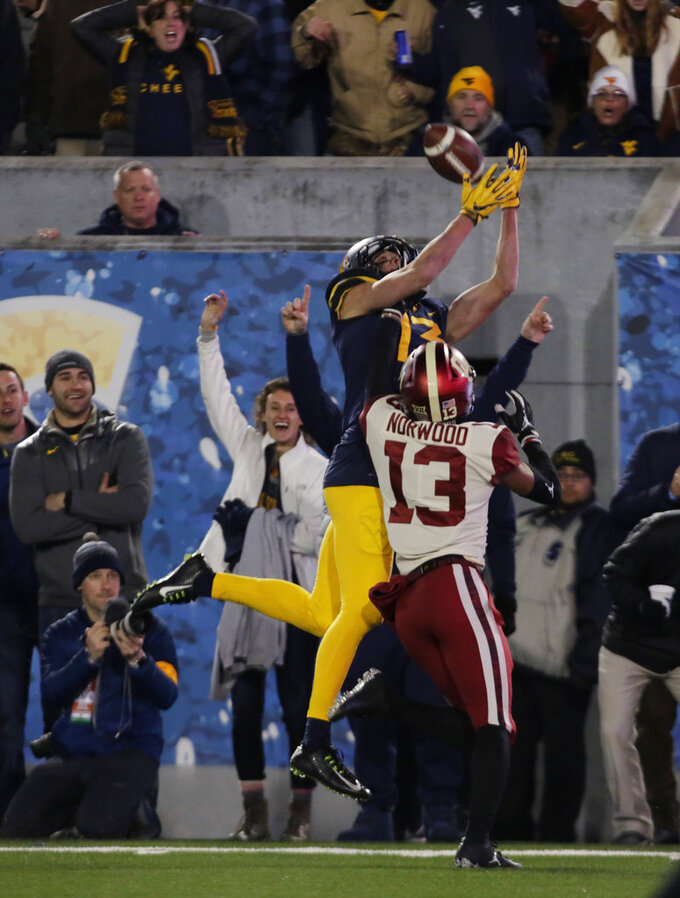 West Virginia wide receiver David Sills V (13) attempts to make a catch while being defended by Oklahoma cornerback Tre Norwood (13) during the first half of an NCAA college football game Friday, Nov. 23, 2018, in Morgantown, W.Va. (AP Photo/Raymond Thompson)