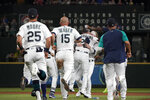 Seattle Mariners' Luis Torrens, center, is mobbed by teammates after he hit a single to score Jarred Kelenic with the winning run during the ninth inning of the team's baseball game against the Texas Rangers, Wednesday, Aug. 11, 2021, in Seattle. The Mariners won 2-1. (AP Photo/Ted S. Warren)