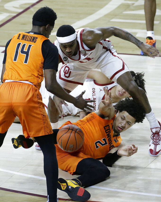 Oklahoma State guard Cade Cunningham (2) passes the ball to guard Bryce Williams (14), away from Oklahoma guard De'Vion Harmon (11) and forward Jalen Hill (1), during the first half of an NCAA college basketball game, Saturday, Feb. 27, 2021, in Norman, Okla. (AP Photo/Garett Fisbeck)