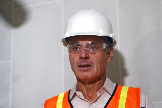 Baseball Commissioner Rob Manfred speaks to the media during a tour of the new under construction Texas Rangers stadium in Arlington, Texas, Tuesday, Nov. 19, 2019. Manfred hopes the investigation into sign stealing by the Houston Astros will be completed by next season and says he has broad authority to impose discipline beyond fines, the loss of amateur draft picks and taking away international signing bonus pool allocation. (AP Photo/LM Otero)