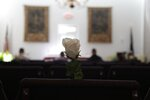 In this Friday, April 3, 2020, photo, a white rose is pinned to an empty chair during J. Robert Coleman's funeral in Lexington, S.C. Thompson Funeral Homes added the flowers to represent the loved ones who couldn't attend in the midst of the coronavirus pandemic. (AP Photo/Sarah Blake Morgan)