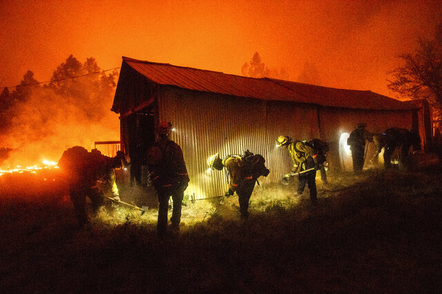 FILE - In this Sept. 9, 2020 file photo, a hand crew clears vegetation from around a barn as the Bear Fire burns through the Berry Creek area of Butte County, Calif. Two years before a deadly fire leveled Berry Creek, the community was selected to receive an $836,000 state grant for pruning vegetation and clearing fuel from potential fire spots. But the forest management project was never completed because of red tape, said local officials, who now wonder if having cleared potential fuel could have changed the fortunes of Berry Creek, the San Francisco Chronicle reported Thursday, Sept. 17, 2020 (AP Photo/Noah Berger, File)