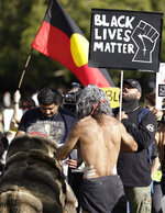 Aboriginal elders carry a small fire during a traditional smoking ceremony as thousands gather at a rally supporting the Black Lives Matter and Black Deaths in Custody movements in Sydney, Sunday, July 5, 2020. (AP Photo/Rick Rycroft)