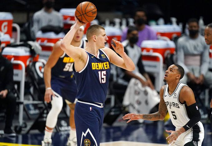 Denver Nuggets center Nikola Jokic, front left, looks to pass the ball as San Antonio Spurs guard Dejounte Murray, right, defends in the first half of an NBA basketball game Friday, April 9, 2021, in Denver. (AP Photo/David Zalubowski)