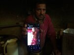 """In this Monday, Aug. 26, 2019, photo, a Kashmiri baker Sonaullah Sofi displays a photograph of his son after he was allegedly tortured by Indian army soldiers at their bakery in the southern village of Parigam, Indian controlled Kashmir. The main city of Indian-controlled Kashmir presents a mostly deserted and subdued look, woven in a maze of razor wire. But drive out into the rural hinterland and residents in village after village narrate horrors of regular nightly raids by Indian army soldiers. Sofi's family was asleep when army troops raided his home. The soldiers took his two sons into a street, hitting them with gun butts, iron chains and sticks, Sofi said. """"Helpless, I heard my sons scream as soldiers started beating them up mercilessly in the middle of the road,"""" Sofi said. ( AP Photo/Aijaz Hussain)"""