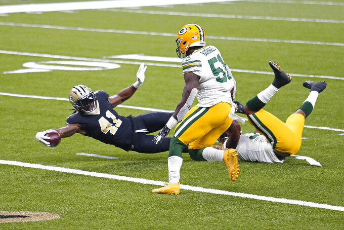 New Orleans Saints running back Alvin Kamara (41) carries for a touchdown against Green Bay Packers strong safety Adrian Amos and inside linebacker Krys Barnes (51) in the first half of an NFL football game in New Orleans, Sunday, Sept. 27, 2020. (AP Photo/Brett Duke)