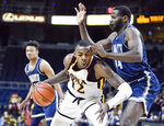 Iona forward Tajuan Agee (12) moves the ball against Monmouth center Sam Ibiezugbe (44) during the first half of the championship NCAA college basketball game during the Metro Atlantic Athletic Conference tournament, Monday, March 11, 2019, in Albany, N.Y. (AP Photo/Hans Pennink)