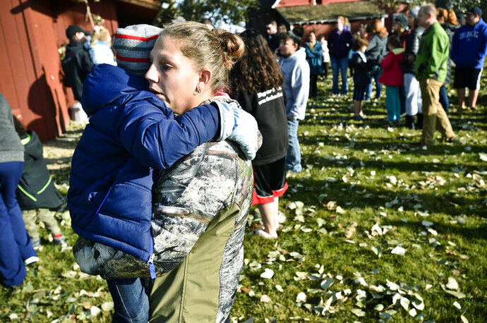 CORRECTS TO SAY WHAT AUTHORITIES THOUGHT WERE THE REMNANTS OF AN EXPLOSIVE DEVICE TURNED OUT TO BE A NONEXPLOSIVE DEVICE - Marnie Wedgwood hugs her son evacuated from the Rossiter Elementary School in Helena, Mont., Tuesday, Oct. 15, 2019, after authorities found what they thought were the remnants of an improvised explosive device on the school playground. Authorities evacuated the elementary school in Montana's capital city Tuesday after officials found the unknown materials, but they turned out to be a plastic bottle filled with nuts and bolts left in the schoolyard. (Thom Bridge/Independent Record via AP)