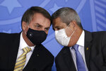 Brazil's President Jair Bolsonaro, left, talks with his Chief of Staff Braga Neto, both wearing masks due to the COVID-19 pandemic, at an event promoting a government campaign against domestic violence at Planalto presidential palace in Brasilia, Brazil, Friday, May 15, 2020. (AP Photo/Eraldo Peres)