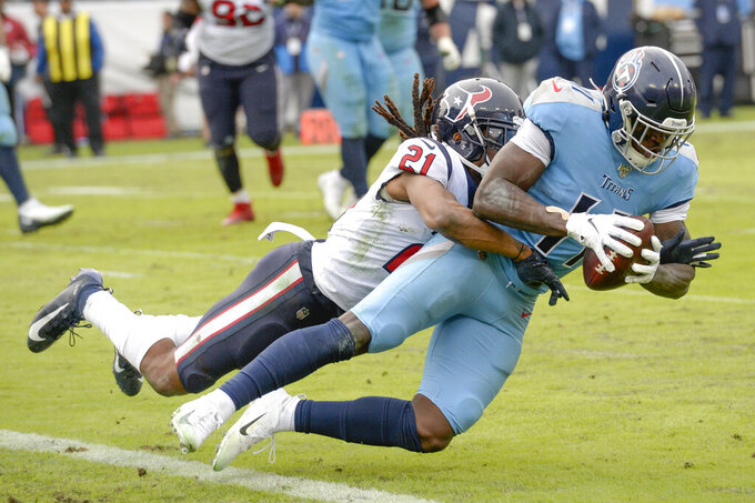Tennessee Titans wide receiver A.J. Brown (11) is hit by Houston Texans cornerback Bradley Roby (21) as Brown scores a touchdown in the second half of an NFL football game Sunday, Dec. 15, 2019, in Nashville, Tenn. (AP Photo/Mark Zaleski)