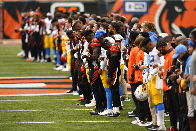 The Cincinnati Bengals and Los Angeles Chargers stand together arm in arm before for an NFL football game, Sunday, Sept. 13, 2020, in Cincinnati. (AP Photo/Bryan Woolston)