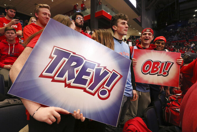 Dayton fans hold signs in support of players Trey Landers and Obi Toppin before the team's NCAA college basketball game against Davidson on Friday, Feb. 28, 2020, in Dayton. (AP Photo/Gary Landers)