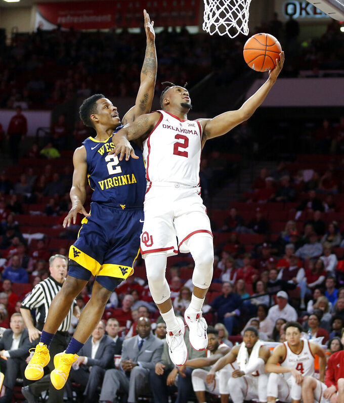 Oklahoma's Aaron Calixte (2) is fouled by West Virginia's Brandon Knapper (2) during an NCAA college basketball game in Norman, Okla., Saturday, March 2, 2019. (Bryan Terry/The Oklahoman via AP)