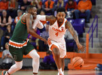 Clemson's Shelton Mitchell drives the ball up the court while defended by Miami's Ja'Quan Newton during the first half of an NCAA college basketball game Saturday, Jan. 13, 2018, in Clemson, S.C. (AP Photo/Richard Shiro)