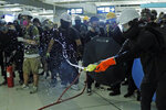 A demonstrator, center, tosses liquid to make the floor slippery during a protest at the Yuen Long MTR station in Hong Kong, Wednesday, Aug. 21, 2019. Hong Kong riot police faced off briefly with protesters occupying a suburban train station Wednesday evening following a commemoration of a violent attack there by masked assailants on supporters of the anti-government movement. (AP Photo/Kin Cheung)