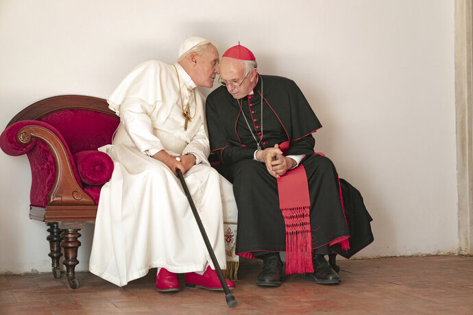 This image released by Netflix shows Jonathan Pryce as Cardinal Bergoglio, right, and Anthony Hopkins as Pope Benedict in a scene from