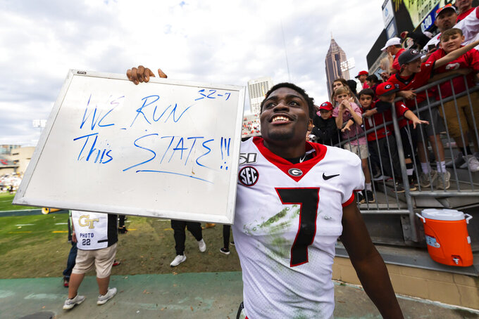 Georgia running back D'Andre Swift holds up a message for fans as he leaves the field after an NCAA college football game against Georgia Tech, Saturday, Nov. 30, 2019 in Atlanta. Georgia won 52-7. (AP Photo/John Amis)
