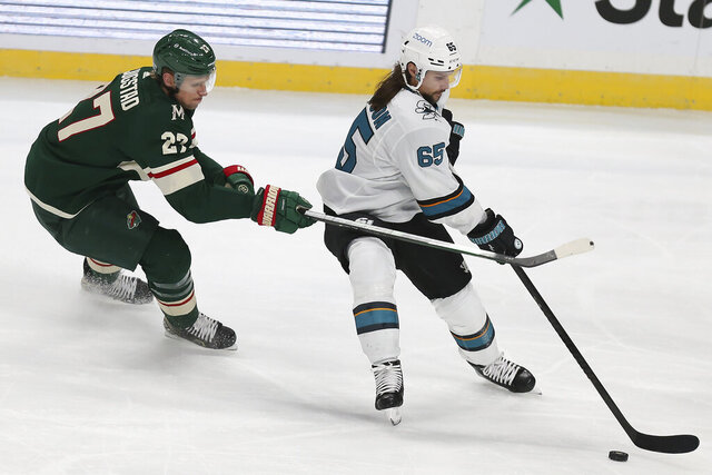 San Jose's Erik Karlsson (65) handles the puck against Minnesota Wild's Nick Bjugstad (27) in the third period of an NHL hockey game Sunday, Jan. 24, 2021, in St. Paul, Minn. San Jose won 5-3. (AP Photo/Stacy Bengs)
