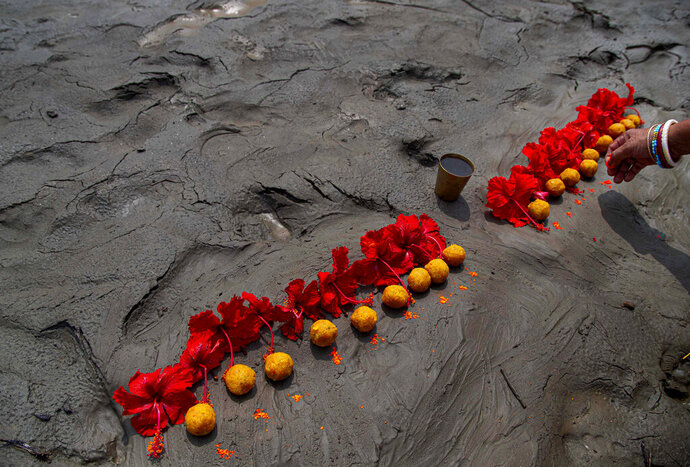 A Hindu woman performs rituals during a prayer ceremony to rid the world of coronavirus, on the banks of the river Brahmaputra in Gauhati, India, Friday, June 5, 2020. (AP Photo/Anupam Nath)