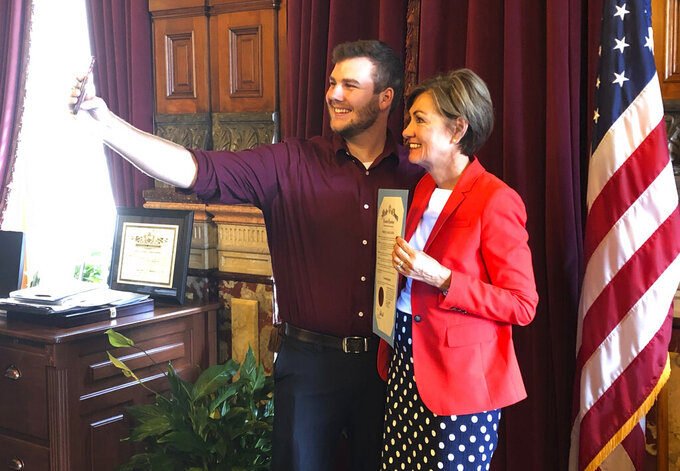 Carson King, of Altoona, Iowa, snaps a selfie Wednesday, Sept. 25, 2019, in the Iowa State Capitol in Des Moines, Iowa, with Iowa Gov. Kim Reynolds, who holds a proclamation declaring Saturday as Carson King Day. The honor was to mark King's plans to donate more than $1 million to charity after his decision to display a hand-written sign before the Sept. 14 Iowa State-Iowa football game seeking money for beer prompted an overwhelming number of donations. (AP Photo/David Pitt)