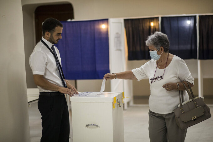 """A woman casts her vote at a polling station during a referendum in Gibraltar, Thursday, June, 24, 2021. Gibraltar is holding a referendum on whether to introduce exceptions to the British territory's ban on abortion. Abortion is illegal in Gibraltar, unless it is needed to save the mother's life. Abortion is legally classified as """"child destruction"""" and is punishable by up to life in prison. (AP Photo/Javier Fergo)"""