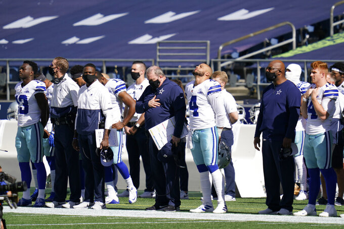Dallas Cowboys quarterback Dak Prescott (4) stands during the national anthem before an NFL football game against the Seattle Seahawks, Sunday, Sept. 27, 2020, in Seattle. (AP Photo/Elaine Thompson)