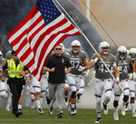 Northwestern's Tyler Gillikin carries the U.S. flag as he leads his team and Northwestern head coach Pat Fitzgerald, second left, on to the field before an NCAA college football game against Duke Saturday, Sept. 8, 2018, in Evanston, Ill. (AP Photo/Jim Young)