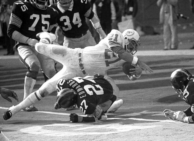 "FILE - In this Dec. 31, 1972, file photo, Miami Dolphins Jim Kiick goes headfirst over Pittsburgh Steelers"" Glen Edwards as Kiick scores in third quarter of the AFC championship game at Pittsburgh's Three Rivers Stadium.  Former running back Kiick, who helped the Dolphins achieve the NFL's only perfect season in 1972, has died at age 73. In recent years Kiick battled memory issues and lived in an assisted living home, and the team announced his death Saturday, June 20, 2020. (AP Photo, File)"