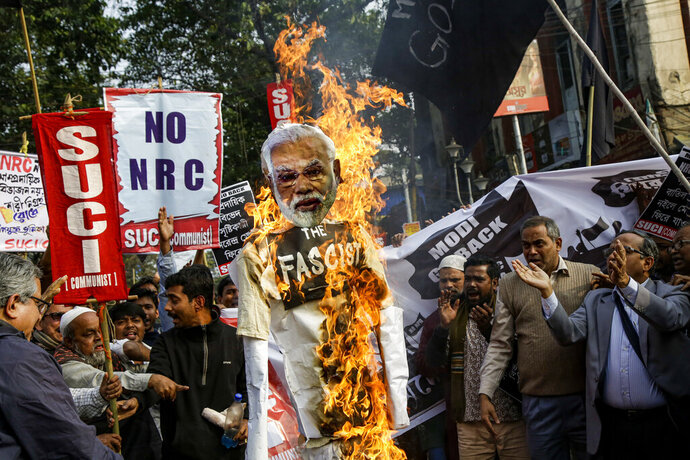 FILE- In this Jan. 11, 2020 file photo, members and activists Socialist Unity Center of India-Marxist (SUCI-M) burn an effigy of Indian Prime Minister Narendra Modi while protesting against a new citizenship law and Prime Minister Narendra Modi's visit, in Kolkata, India. The head of Indian Prime Minister Narendra Modi's Hindu nationalist Bharatiya Janata Party in the state of West Bengal has threatened to shoot and jail people who protest a new citizenship law that has triggered a month of nationwide demonstrations. (AP Photo/Bikas Das, File)