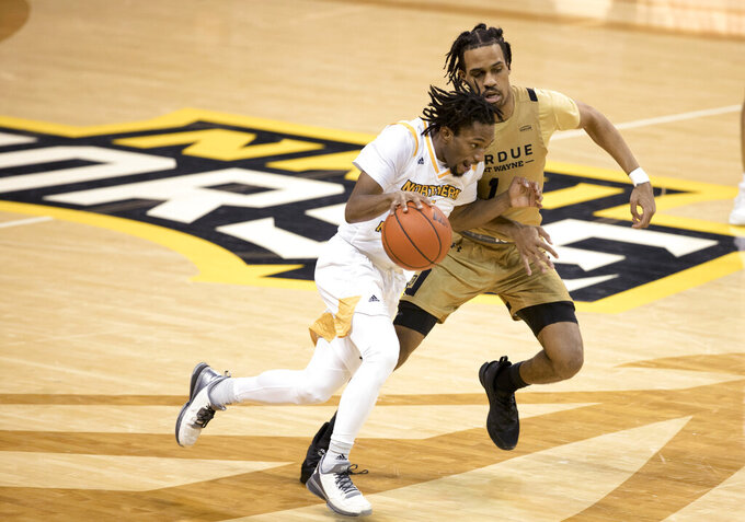 Northern Kentucky guard Bryson Langdon (11) drives on Purdue-Fort Wayne guard Jarred Godfrey (1) during the second half of an NCAA college basketball game Friday, Jan. 1, 2021, in Highland Heights, Ky. (Albert Cesare/The Cincinnati Enquirer via AP)