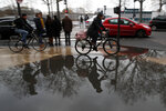 Bicycles riders are reflected in the water in Paris, Saturday, Dec. 7, 2019. French strikes are disrupting weekend travel around the country, as truckers blocked highways and most trains remained at a standstill because of worker anger at President Emmanuel Macron's policies as a mass movement against the government's plan to redesign the national retirement system entered a third day. (AP Photo/Francois Mori)