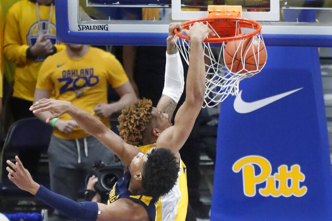 Pittsburgh's Terrell Brown, top, dunks behind West Virginia's Miles McBride during the second half of an NCAA college basketball game, Friday, Nov. 15, 2019, in Pittsburgh. (AP Photo/Keith Srakocic)