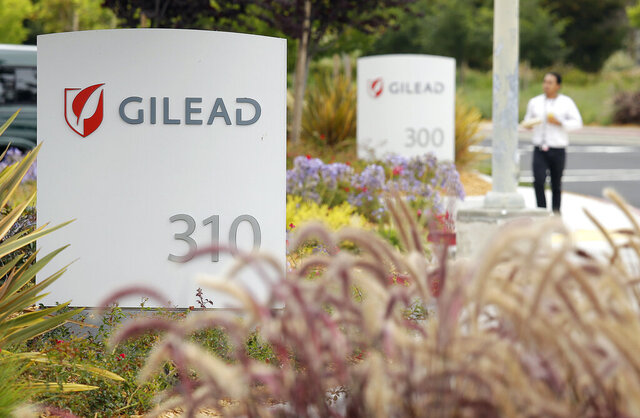FILE - In this July 9, 2015, file photo, a man walks outside the headquarters of Gilead Sciences in Foster City, Calif. Gilead Sciences said Wednesday, March 25, 2020 it will give up the specialty status it received days earlier for its COVID-19 drug amid public outrage that the company was seeking to boost the profits of its treatment. (AP Photo/Eric Risberg, File)