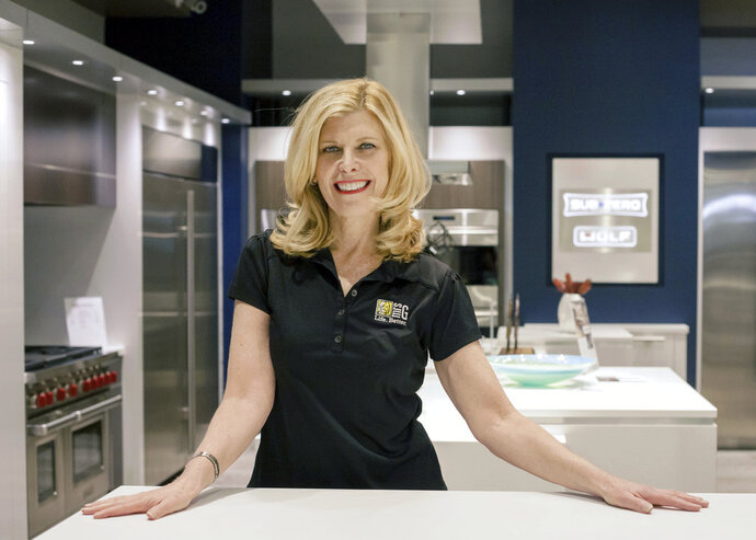 """In this March 11, 2018, photo provided by Mrs. G Inc., Debbie Schaeffer, owner of Mrs. G, an appliance retailer in Lawrence Township, N.J., poses for a photo at the retailers Sub-Zero Wolf Living Kitchen display. A slowdown in home sales is creating opportunities for small businesses like home renovators and appliance dealers. """"People are confident and spending money and reinvesting in their homes,"""" Schaeffer said. (Ashlee Cain/Mrs. G Inc. via AP)"""