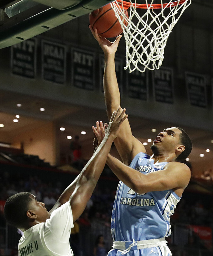 North Carolina forward Garrison Brooks shoots and scores over Miami guard Anthony Lawrence II during the first half of an NCAA college basketball game on Saturday, Jan. 19, 2019, in Coral Gables, Fla. (AP Photo/Brynn Anderson)