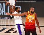 Los Angeles Lakers forward Anthony Davis (3) makes a three-point basket over Utah Jazz center Rudy Gobert (27) during the first half of an NBA basketball game Monday, Aug. 3, 2020, in Lake Buena Vista, Fla. (Kim Klement/Pool Photo via AP)