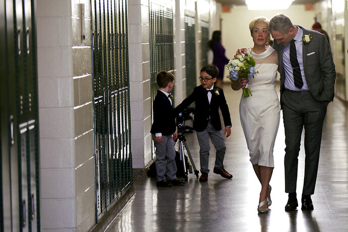 In this Saturday, March 10, 2018 photo, Jenn Sudol and Chris Gash walk near their old high school lockers during their wedding at Clifton High School, in Clifton, N.J. The couple met in 1989 when they were freshman at the school.  (Anne-Marie Caruso /The Record via AP)