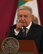 Mexican President Andres Manuel Lopez Obrador gives his daily, morning news conference at the presidential palace, Palacio Nacional, in Mexico City, Friday, Oct. 16, 2020. López Obrador said Friday that his ambassador to the United States told him two weeks ago that there was an investigation underway there involving Mexico's former defense secretary, retired Gen. Salvador Cienfuegos, who was arrested Thursday in Los Angeles. (AP Photo/Marco Ugarte)