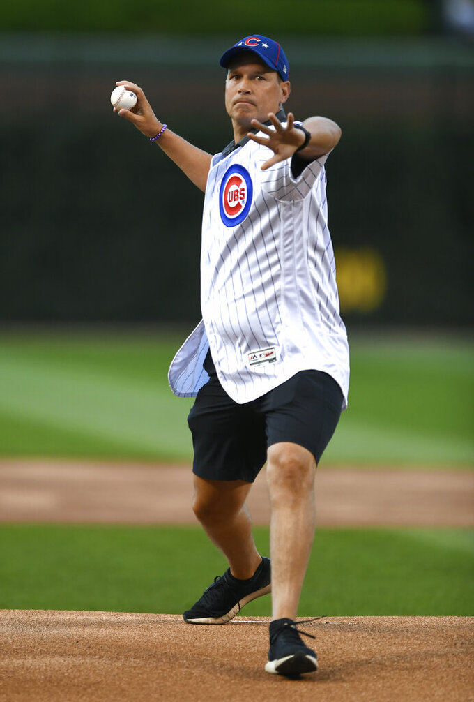 Northwestern men's basketball coach Chris Collins throws out a ceremonial first pitch before a baseball game between the Chicago Cubs and the Atlanta Braves on Wednesday, June 26, 2019, in Chicago. (AP Photo/Paul Beaty)