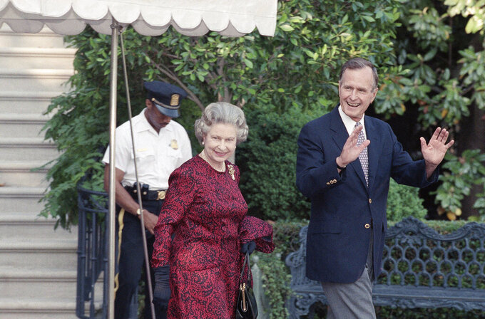 FILE - In this May 15, 1991 file photo, U.S. President George H.W. Bush escorts Queen Elizabeth II from the White House to a helicopter en route to Baltimore to watch her first major league baseball game, in Washington. (AP Photo/Doug Mills, File)